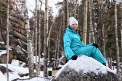 Girl in blue sportswear sitting on a large boulder on the nature on the background of rocks in the winter stock image