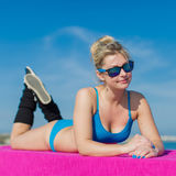 Girl in blue sportswear and sunglasses lying on front outdoors Royalty Free Stock Images