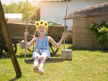 The girl in the blue suit fun swinging on the village swing. Beautiful girl in the rays of the sun with the decoration of flowers on her head on the old swing Royalty Free Stock Image