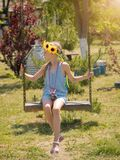 The girl in the blue suit swinging on the old swing on a Sunny d. Beautiful girl in the rays of the sun with the decoration of flowers on her head on the old Royalty Free Stock Image