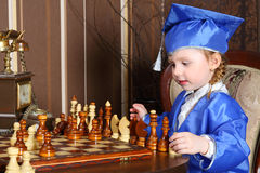 Girl in blue suits play chess Royalty Free Stock Photography
