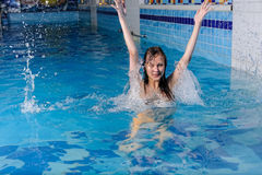 Girl in blue swimming pool with splash and drops Royalty Free Stock Image