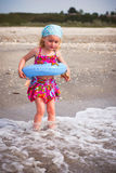 Girl with blue swimming ring. Gorgeous baby girl playing at the seaside Royalty Free Stock Photography