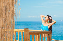 Girl in blue swimsuit sunbathing on the sea in the bungalow Stock Photography