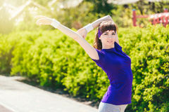 Girl in a blue T-shirt is doing sports in nature against the backdrop of bushes.young woman jogging in the park Royalty Free Stock Photo