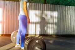 A girl in a blue T-shirt and tights stands in an open gym in fro royalty free stock photos
