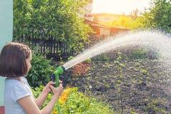 Girl watering a garden from a hose stock photos