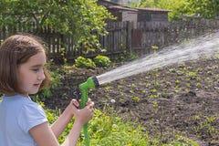 Girl watering a garden from a hose royalty free stock photos