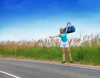 The girl in a blue t-shirt and white shorts stops a passing car on the road to the sunny summer day Stock Photo