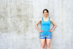 Girl in blue tank top and shorts over the wall smiling. Royalty Free Stock Photography