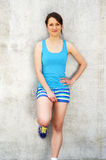 Girl in blue tank top and shorts over the wall smiling. Stock Image
