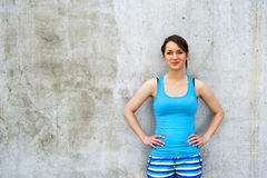 Girl in blue tank top and shorts over the wall smiling. Stock Photos