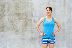 Girl in blue tank top and shorts over the wall smiling. Royalty Free Stock Photo