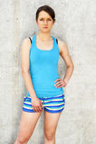 Girl in blue tank top and shorts over the wall smiling. Royalty Free Stock Image