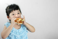 Girl in Blue Thai Dress Eating a Hamburger With intent fun. Royalty Free Stock Image