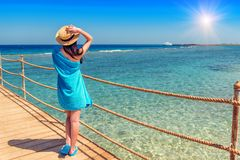 Girl with blue towel on the pier. Girl in streaw hat with blue towel on the wooden pier Stock Image