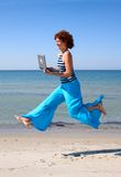 Girl in blue trousers running with laptop Royalty Free Stock Image