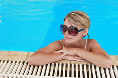 Girl in blue water pool in glasses Sun Protection Royalty Free Stock Image