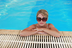 Girl in blue water pool in glasses Sun Protection Royalty Free Stock Images