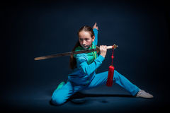 Girl in a blue wear engaged wushu Royalty Free Stock Image