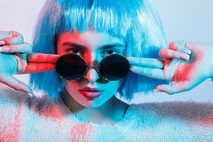 Girl in blue wig. Serious girl in blue wig and sunglasses on multicolor background looking at camera Royalty Free Stock Images