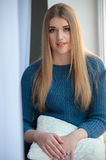 Girl in a blue woolen sweater sitting at the window Royalty Free Stock Image