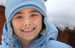 Girl in blue wooly hat smiling Stock Photography