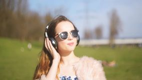 Girl in bluetooth headphones, sings and dances outside. A sweet girl with long hair, and sunglasses dancing and sweat in the park,