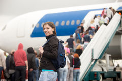 Girl boarding airplane. Young Caucasian happy smiling woman passenger in 20s travelling with backpack, boarding airplane, looking at camera, people climbing air Royalty Free Stock Image