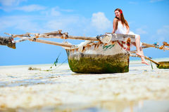 Girl on boat. Beautiful girl sitting on boat at tropical beach of Zanzibar island royalty free stock images