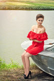 Girl on the boat near the lake in summer5. Girl on the boat near the lake in summer in red dress Royalty Free Stock Image