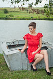 Girl on the boat near the lake in summer10. Girl on the boat near the lake in summer in red dress Royalty Free Stock Photos