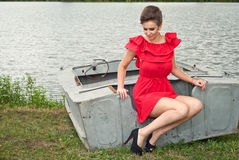 Girl on the boat near the lake in summer13. Girl on the boat near the lake in summer in red dress Stock Photos