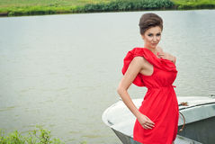 Girl on the boat near the lake in summer8. Girl on the boat near the lake in summer in red dress Stock Photos