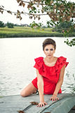 Girl on the boat near the lake in summer. In red dress Stock Photography
