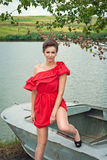 Girl on the boat near the lake in summer9. Girl on the boat near the lake in summer in red dress Stock Photography