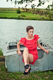 Girl on the boat near the lake in summer11. Girl on the boat near the lake in summer in red dress Stock Photos