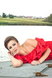 Girl on the boat near the lake in summer15. Girl on the boat near the lake in summer in red dress Royalty Free Stock Photo