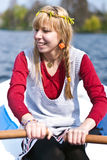 Girl in a boat rowing. Beautiful blond girl in a boat rowing and having fun on the water with a clear blue sky Stock Images