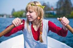Girl in a boat rowing. Beautiful blond girl in a boat rowing and having fun on the water with a clear blue sky, focus on hands Stock Images