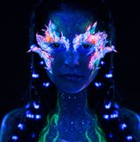Girl with body art. Portrait of beautiful woman with body art glowing in ultraviolet light Stock Photos