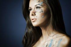 Girl with bodyartposing on blue Stock Image