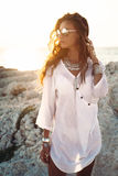 Girl in boho style. Beautiful boho styled girl wearing white shirt with fashion ethnic jewelery and flash tattoo at the beach in sunlight royalty free stock photo