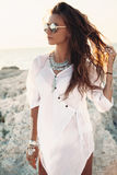 Girl in boho style. Beautiful boho styled girl wearing white shirt with fashion ethnic jewelery and flash tattoo at the beach in sunlight stock image