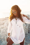 Girl in boho style. Beautiful boho styled girl wearing white shirt with fashion ethnic jewelery and flash tattoo at the beach in sunlight royalty free stock images
