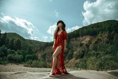 The girl in the boho style. A sexe girl in a red dress is walking along the rocks near the river. In the background is the Carpathians mountains. Creative colors stock photo