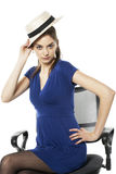 Girl with bonnet. Girl  posing on chair with bonnet in hand Stock Photography