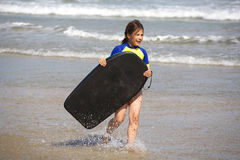 Girl with boogie board at beach Stock Image