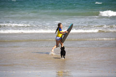 Girl with boogie board at beach. A little girl running through the water with her boogie board and her poodle royalty free stock photography