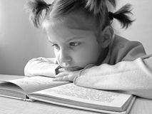 Girl with book 1. Small pretty reading girl black and white portrait Royalty Free Stock Images